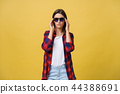 Portrait of a beautiful girl in round glasses on a yellow background in the studio. 44388691