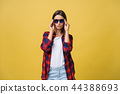 Portrait of a beautiful girl in round glasses on a yellow background in the studio. 44388693