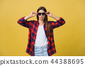 Portrait of a beautiful girl in round glasses on a yellow background in the studio. 44388695