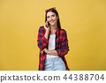 Portrait of a pensive young girl calling on mobile phone while standing and looking away isolated 44388704