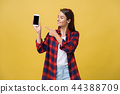 Portrait of a happy young girl dressed in summer pointing finger at blank screen mobile phone 44388709