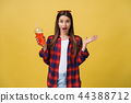 Fashion pretty young woman with fresh fruit juice cup in casual cloth having fun over colorful 44388712
