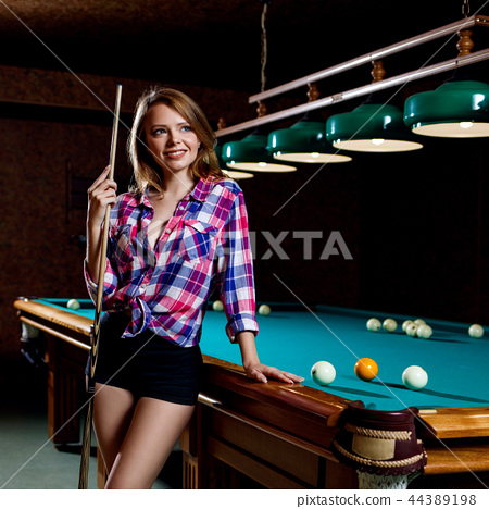 Beautiful woman stands near billiards table with cue. 44389198