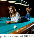 Young woman lying on the green billiard table. 44389213