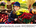 Smiling child with basket of red apples sitting in autumn park 44390047