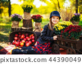 Smiling child with basket of red apples sitting in autumn park 44390049