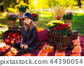 Smiling child with basket of red apples sitting in autumn park 44390054