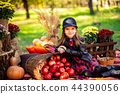 Smiling child with basket of red apples sitting in autumn park 44390056