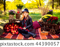 Smiling child with basket of red apples sitting in autumn park 44390057