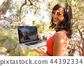 Happy woman using laptop at garden. 44392334