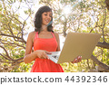 Happy woman using laptop at garden. 44392346