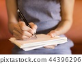 Women holding a pen writing a notebook papers. 44396296