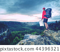 Tall tourist with backpack looking in paper map 44396321