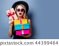 girl in black dress and hat with gift boxes 44399464