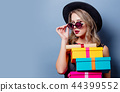 girl in black dress and hat with gift boxes 44399552