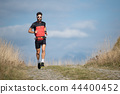 An athlete runner with a beard trains  44400452