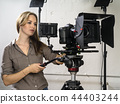 Attractive woman operating a video camera rig 44403244