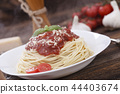 Warm, delicious spaghetti with sauce and basil. 44403674