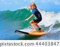 Young surfer rides on surfboard on sea waves 44403847