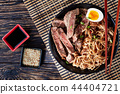 a bowl of soba with sliced roast beef 44404721