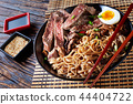 a bowl of soba with sliced roast beef 44404722