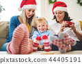 A small boy with mother and grandmother with Santa hat at home at Christmas time. 44405191