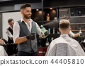 Smiling barber sprinkling water on client's haircut using sprayer bottle. 44405810