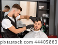 Confident barber shaving client's beard with sharp razor. 44405863
