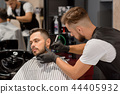 Barber concentrated on shaving man's beard using sharp razor. 44405932