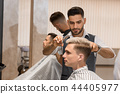 Barber concentrated on shaving man's beard using sharp razor.  44405977