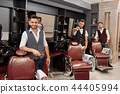 Three handsome barbers posing in barbershop near hairdresser chairs. 44405994