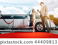 Driver helping VIP woman or star out of limo on red carpet 44409813
