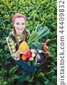 Farmer woman in a field offering organic vegetables  44409832