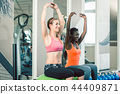 Full length of two fit women sitting on fitness balls while exercising 44409871