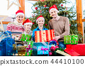 Mum, dad and sons on X-mas during handing out of presents 44410100