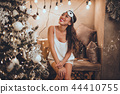 Beautiful asian woman is wearing sleeping mask and pajamas at home near christmas tree in cozy 44410755