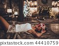 Beautiful asian woman is lying in bed and wearing sleeping mask at home near christmas tree in cozy 44410759
