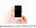 Woman hand holding white mobile phone 44412276