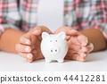 Woman hand holding piggy bank. Saving money 44412281