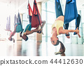Fit young woman practicing aerial yoga during group class 44412630