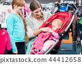 Girl looking at mother taking care of baby in shop 44412658