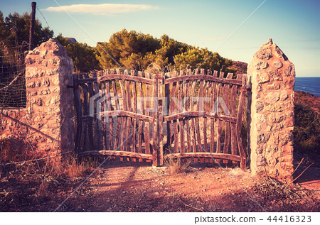 Old wooden closed fence at sunset. 44416323
