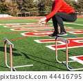 Athlete jumping over hurdles on turf field 44416795