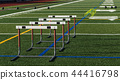 field with hurldes and medicine balls for practice 44416798