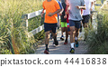 Group of boys running on a boardwalk at the beach 44416838