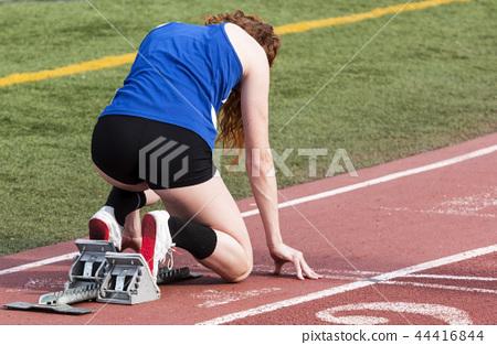 High school female runner in the starting blocks 44416844