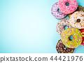 Donuts glazed with sprinkles on pastel blue background. 44421976
