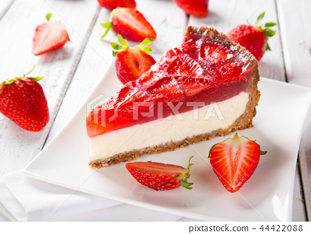 Delicious cheesecake with strawberries on wooden table. 44422088