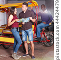 Young couple standing near rickshaw cycle before touristic tour 44424479