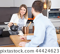 Woman pouring coffee to man 44424623